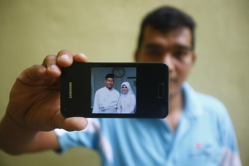 Mohamad shows a wedding picture that he took of Razahan and Norli on his mobile phone during an interview near his house in Kuala Lumpur