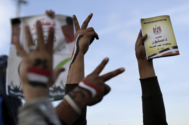 Supporters of President Mohammed Morsi with the Egyptian national flag painted on their hands, flash victory signs as one holds a copy of Egypt's draft constitution, right, during a demonstration, in Cairo, Egypt, Tuesday, Dec. 11, 2012. Islamists led by Morsi's Muslim Brotherhood group have called a demonstration to back the president's decision to hold a referendum on the new constitution on December 15. Opposition groups have rejected the constitution as undemocratic and want the vote canceled. (AP Photo/Hassan Ammar)