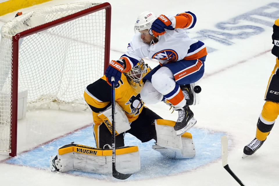 New York Islanders' Leo Komarov (47) leaps but can't get out of the way of a shot in front of Pittsburgh Penguins goaltender Tristan Jarry during the third period in Game 1 of an NHL hockey Stanley Cup first-round playoff series in Pittsburgh, Sunday, May 16, 2021. (AP Photo/Gene J. Puskar)