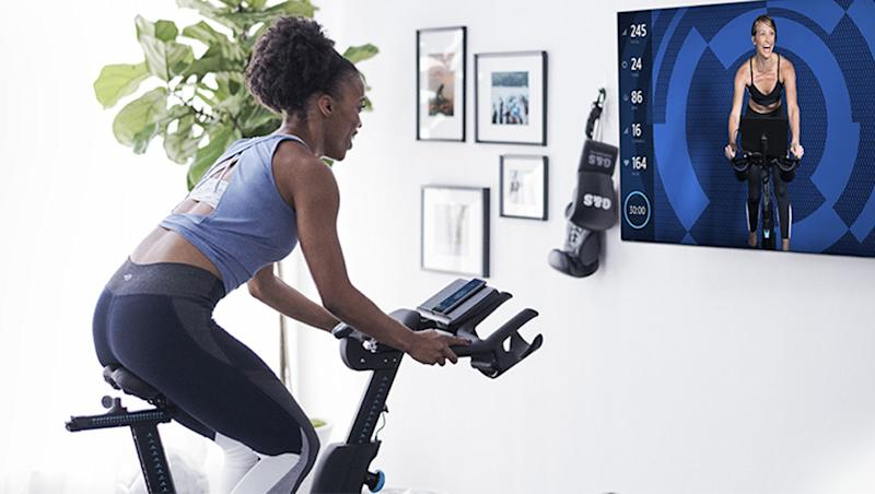 A woman rides a connected exercise bike.