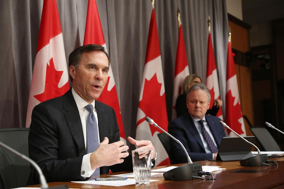 Canada's Finance Minister Bill Morneau (L) speaks during a news conference March 18, 2020 in Ottawa, Ontario, as Bank of Canada Governor Stephen Poloz looks on. - Canadian Prime Minister Justin Trudeau announced Can$27 billion in direct aid on March 18, 2020 to help workers and businesses cope with the economic impacts of the coronavirus pandemic.He said tax payments worth an estimated Can$55 billion could be deferred until August. (Photo by Dave Chan / AFP) (Photo by DAVE CHAN/AFP via Getty Images)