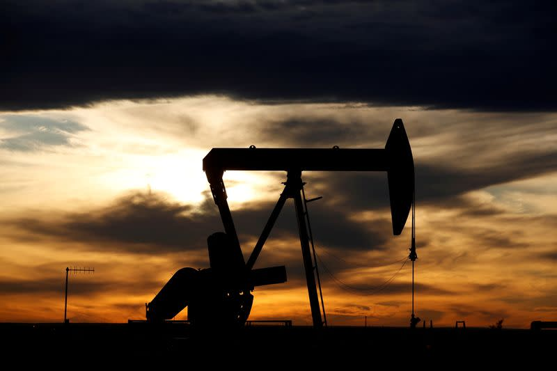 FILE PHOTO: The sun sets behind a crude oil pump jack on a drill pad in the Permian Basin in Loving County