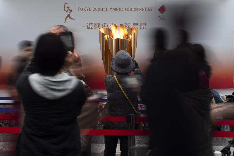 FILE - In this March 24, 2020, file photo, people take pictures of the Olympic Flame during a ceremony in Fukushima City, Japan. The Olympic flame has been removed from public display in Japan and it's not clear when it will reappear again or where. The flame arrived in Japan from Greece on March 26. (AP Photo/Jae C. Hong, File)