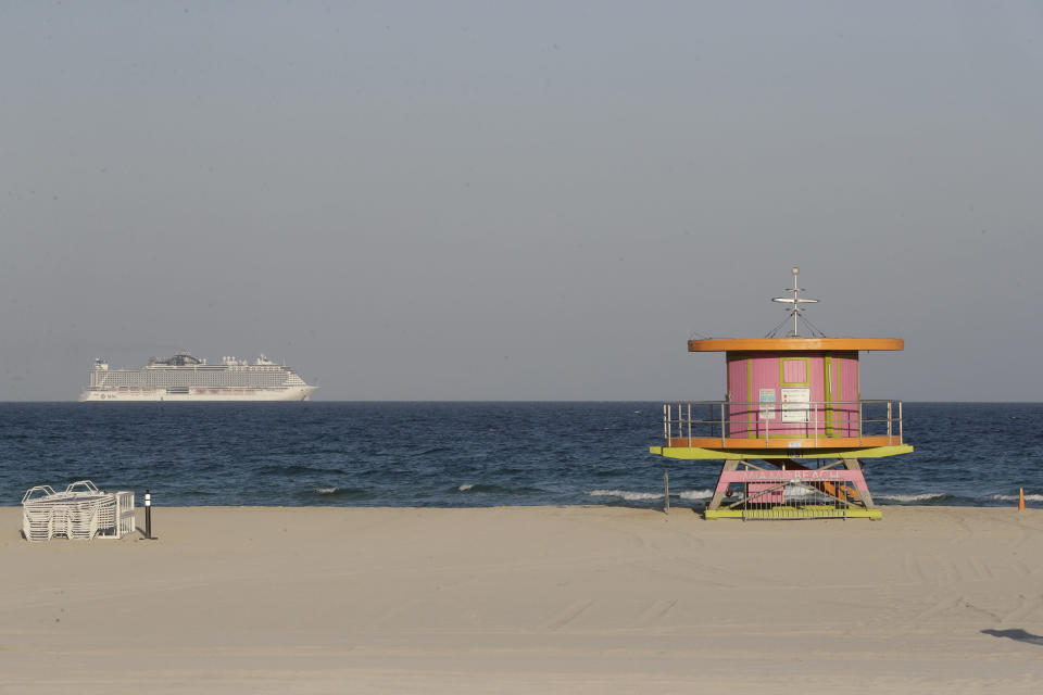 A cruise ship is shown out at sea, beyond a lifeguard tower along a closed beach Wednesday, March 25, 2020, in Miami Beach, Fl. (AP Photo/Wilfredo Lee)