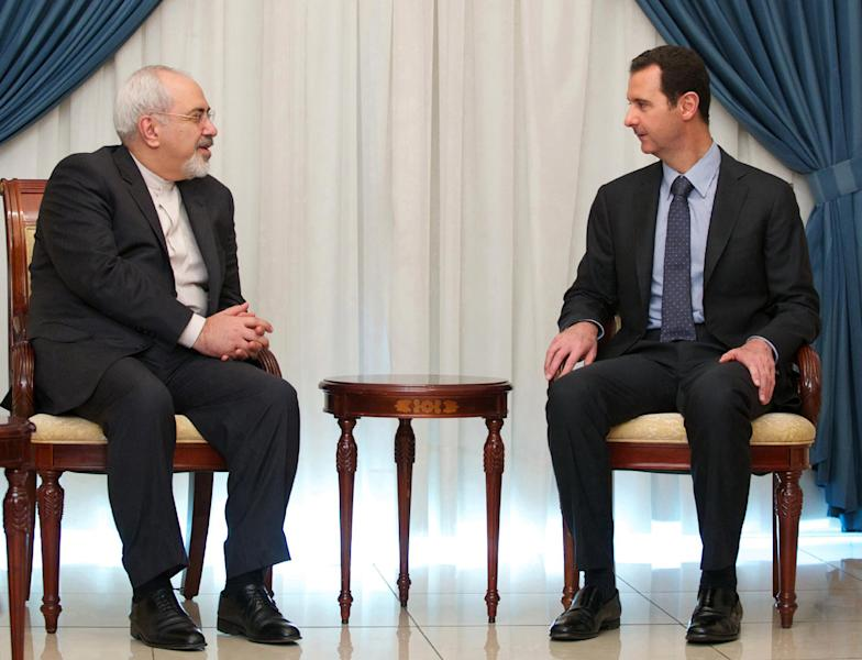 In this photo released by the Syrian official news agency SANA, Iranian Foreign Minister Mohammad Javad Zarif, left, meets with Syrian President Bashar Assad, right, in Damascus, Syria, Wednesday, Jan. 15, 2014. Assad and Zarif have held talks about next week's United Nations conference in Montreux, Switzerland, aimed at trying to resolve the three-year deadly conflict. (AP Photo/SANA)