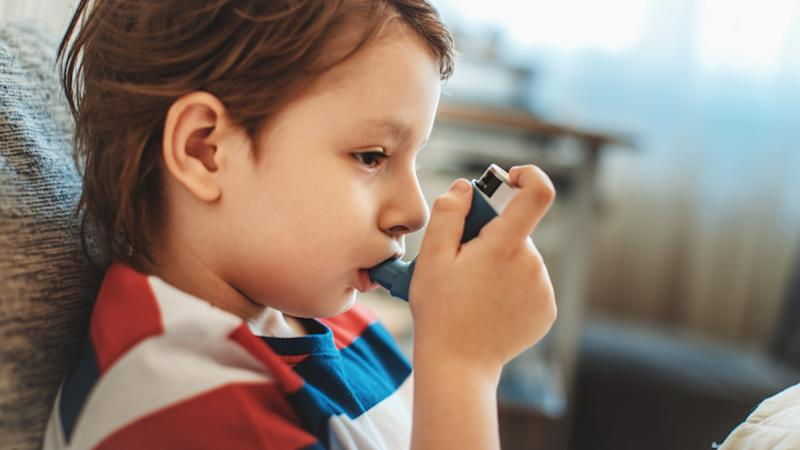 A file picture of a boy using an asthma puffer.