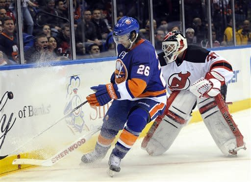 New Jersey Devils goalie Martin Brodeur (30) drives the puck away from New York Islanders' Matt Moulson (26) in the second period of an NHL hockey game on Saturday Jan., 19, 2013 at Nassau Coliseum in Uniondale, N.Y. (AP Photo/Kathy Kmonicek)