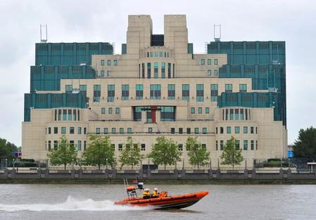 FILE PHOTO: A motorboat passes by the MI6 building in London