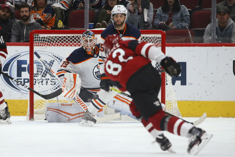 Edmonton Oilers goalie Mikko Koskinen (19) and defenseman Darnell Nurse (25) wait on a shot from Arizona Coyotes defenseman Jordan Oesterle (82) during the second period of an NHL hockey game Tuesday, Feb. 4, 2020, in Glendale, Ariz. The Coyotes won 3-0. (AP Photo/Ross D. Franklin)