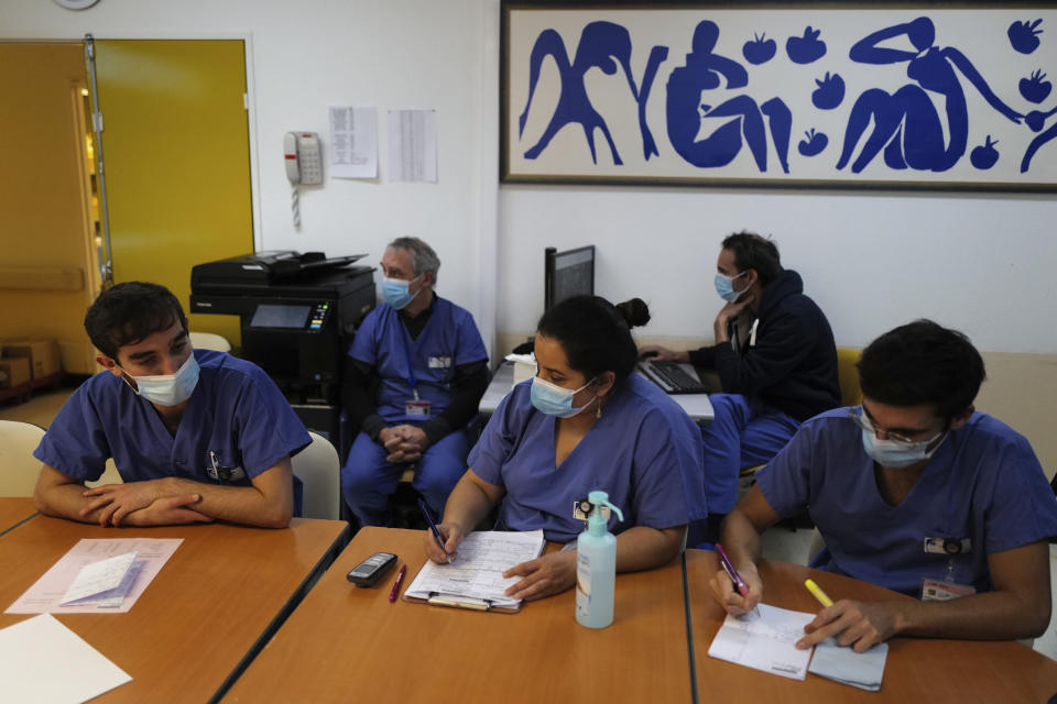Medical staff, including Dr. Philippe Montravers, second left, attend a morning meeting, at Bichat Hospital, AP-HP, in Paris Tuesday, Dec. 1, 2020. One of the biggest hospitals in Paris, Bichat Hospital, this month reopened all 22 of its operating rooms. It is once again performing surgeries that were stopped during virus surges that pushed France's death toll past 55,000. (AP Photo/Francois Mori)