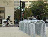 A lone cyclist waits for a traffic signal near empty bicycle racks in the Federal Center Plaza area during day three of the U.S. government shutdown in Washington October 3, 2013. REUTERS/Gary Cameron