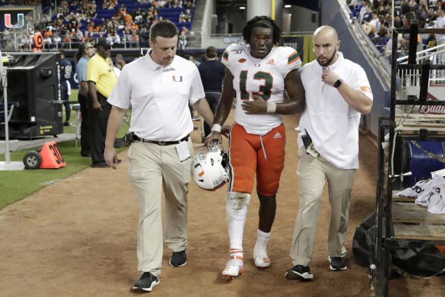 Miami running back DeeJay Dallas (13) leaves the field after an injury during the second half of an NCAA college football game against FIU, Saturday, Nov. 23, 2019, in Miami. FIU won 30-24. (AP Photo/Lynne Sladky)