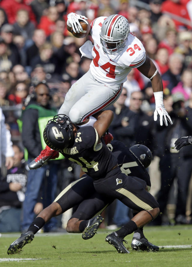Ohio State running back Carlos Hyde, top, leaps over Purdue defensive back Frankie Williams, left, and safety Taylor Richards (4) during the first half of an NCAA college football game in West Lafayette, Ind., Saturday, Nov. 2, 2013. (AP Photo/Michael Conroy)