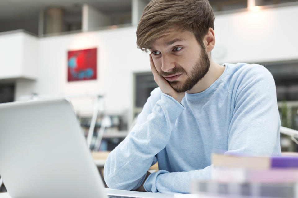 Student using laptop in a university library