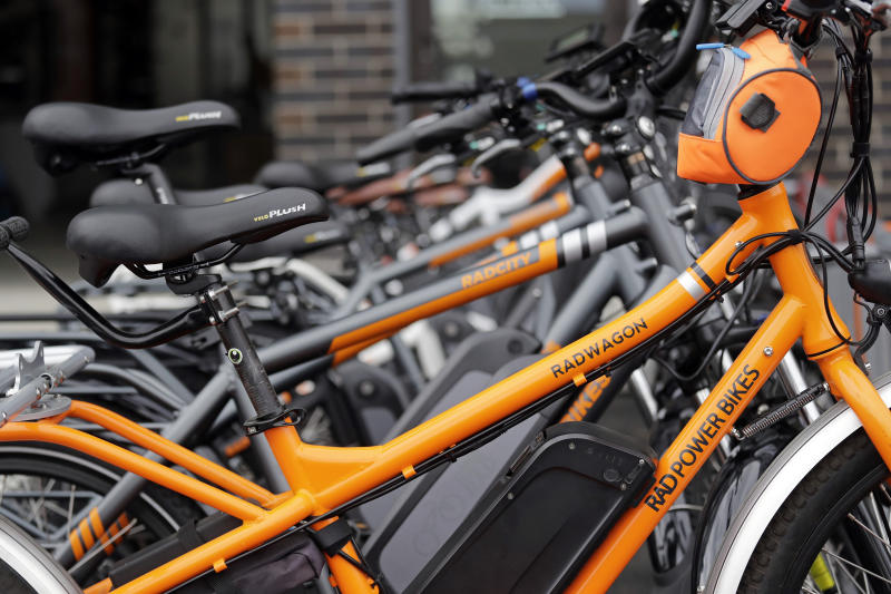In this photo taken Wednesday, May 15, 2019, electric bicycles are lined-up outside Rad Power Bikes in Seattle, where the bicycle company said that they will absorb 100% of any tariff on their Chinese-made bicycles. From airplanes made by Boeing to apples, cherries and wheat grown by farmers, no other state is more dependent on international trade than Washington. As the tariff disputes escalate, small factories are closing and manufacturing behemoths like Boeing are increasingly worried about access to crucial Asian markets that have helped propel the state's booming economy. (AP Photo/Elaine Thompson)