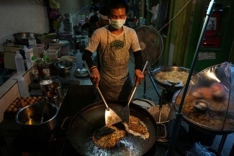 A man prepares food at a street stall in the Phrakanong district of Bangkok