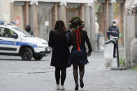 FILE - In this March 17, 2021 file photo, a newly university graduated student, wearing a crown of flowers, walks with a friend, in Rome. Backed by 261 billion euros from the EU and Italian government, the country's recovery plan calls for a top-to-bottom shakeup of a major industrial economy long hampered by red tape, a fear of change, and bureaucratic and educational inertia. Leading the charge is Premier Mario Draghi, the former head of the European Central Bank, who was tapped as head of a national unity government specifically for his economic expertise and institutional knowledge both in Italy and the EU. A key target is keeping more young Italians from taking their know-how abroad, a perennial issue in Italy, which has one of the lowest rates of university graduates in Europe and one of the largest brain drains. (AP Photo/Gregorio Borgia file)