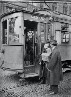 """<span class=""""caption"""">Precautions taken during the 1918 flu pandemic would not allow anyone to ride street cars without a mask. Here, a conductor bars an unmasked passenger from boarding.</span> <span class=""""attribution""""><a class=""""link rapid-noclick-resp"""" href=""""https://www.gettyimages.com/detail/news-photo/precautions-taken-during-spanish-influenza-epidemic-would-news-photo/1223011380"""" rel=""""nofollow noopener"""" target=""""_blank"""" data-ylk=""""slk:Universal History Archive/Getty Images"""">Universal History Archive/Getty Images</a></span>"""