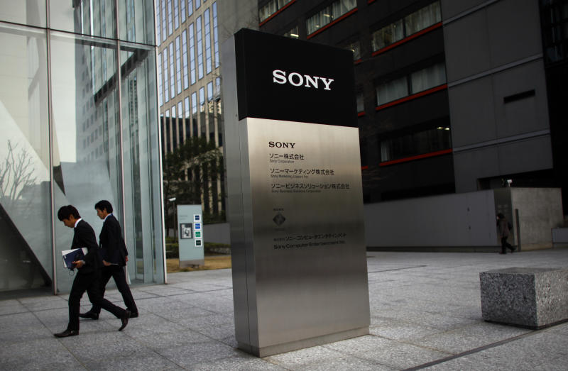 People walk outside Sony head office in Tokyo Thursday, Feb. 7, 2013. Sony Corp. is still struggling but managed to reduce its red ink for the latest quarter as the Japanese electronics and entertainment company aims for a comeback from record yearly losses. (AP Photo/Junji Kurokawa)
