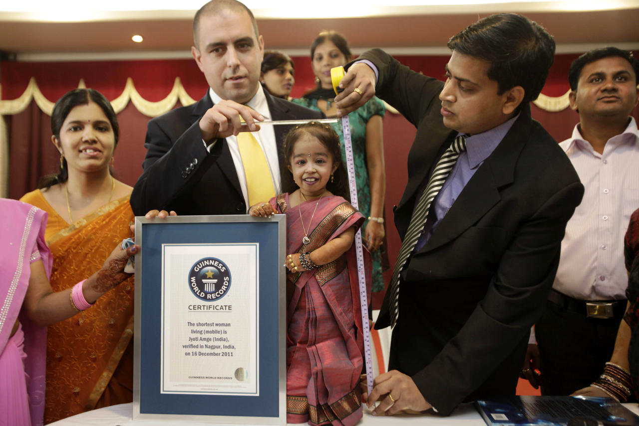 "Guinness World Records adjudicator Rob Molloy, center, and Dr. Manoj Pahukar of Wockhardt hospital, right, measures Jyoti Amge in Nagpur, India, Friday, Dec. 16, 2011. Amge, 18, is now eligible under the Guinness World Record guidelines for the ""Shortest Woman in the world"" title measuring 61.95 centimeters (2 feet). (AP Photo/Manish Swarup)"