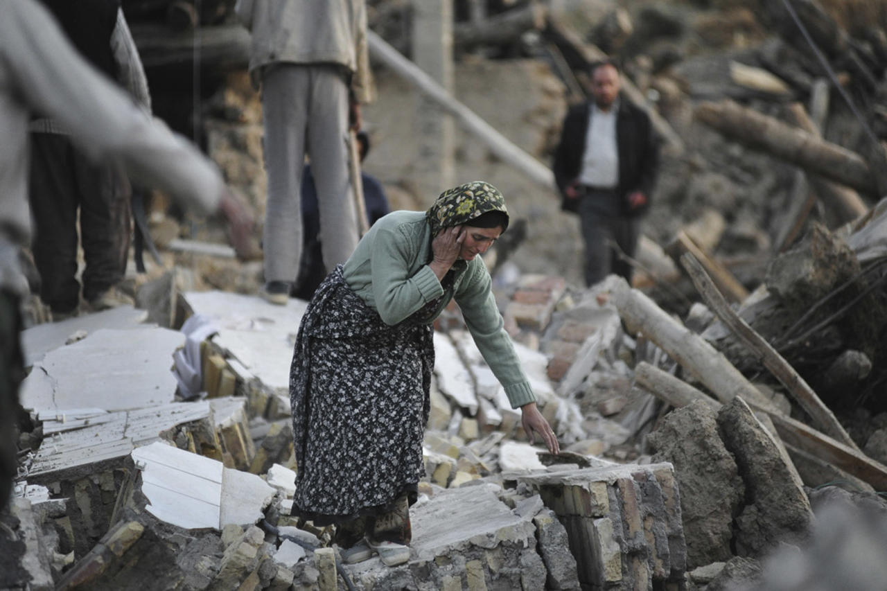 A female victim of Saturday's earthquake makes her way on the ruins of buildings in a village near the city of Varzaqan in northwestern Iran, Sunday, Aug. 12, 2012. Twin earthquakes in Iran have killed at least 250 people and injured over 2,000, Iranian state television said on Sunday, after thousands spent the night outdoors after their villages were leveled and homes damaged in the country's northwest. Iran is located on seismic fault lines and is prone to earthquakes. It experiences at least one earthquake every day on average, although the vast majority are so small they go unnoticed. (AP Photo/Mehr News Agency, Mahsa Jamali)