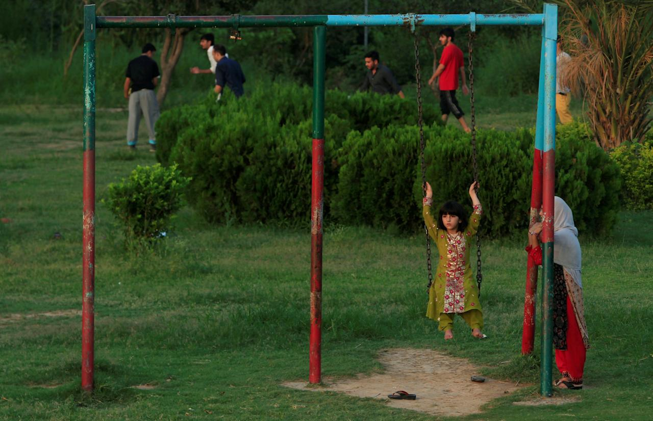 A girl rides on a swing at a park in Islamabad, Pakistan July 29, 2016. REUTERS/Faisal Mahmood