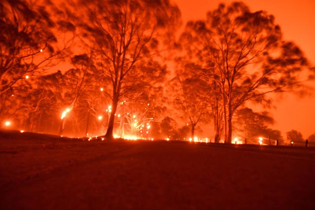 The afternoon sky glows orange from bushfires in the area around the town of Nowra in New South Wales (Saeed Khan/AFP via Getty Images)