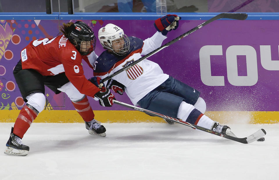 Alex Carpenter of the United States (25) looses her footing under pressure from Jocelyne Larocque of Canada (3) during the second period of the women's gold medal ice hockey game at the 2014 Winter Olympics, Thursday, Feb. 20, 2014, in Sochi, Russia. (AP Photo/Petr David Josek)