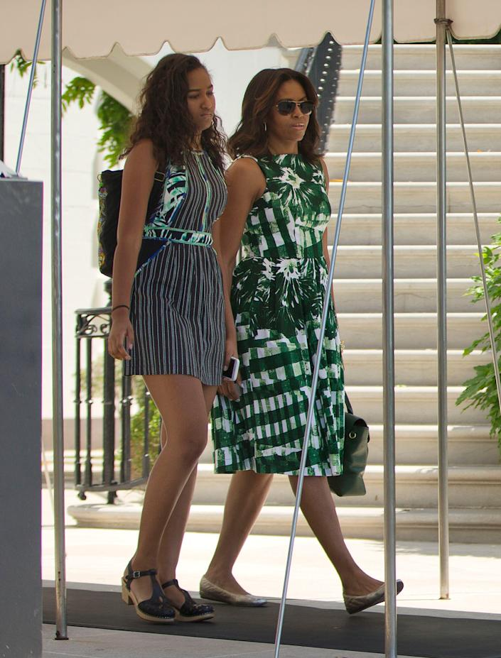 First lady Michelle Obama walks with her daughter Sasha to the South Lawn of the White House in Washington on June 17, 2016, before boarding Marine One for the short flight to Andrews Air Force Base, Md.