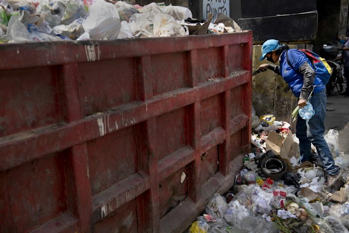 "A person digs into the garbage for food March 23 in Caracas, Venezuela. While President Nicolás Maduro declared a national quarantine, the international community is concerned about how the country will control the pandemic with its increasing levels of poverty. <span class=""copyright"">(Carlos Becerra / Getty Images)</span>"