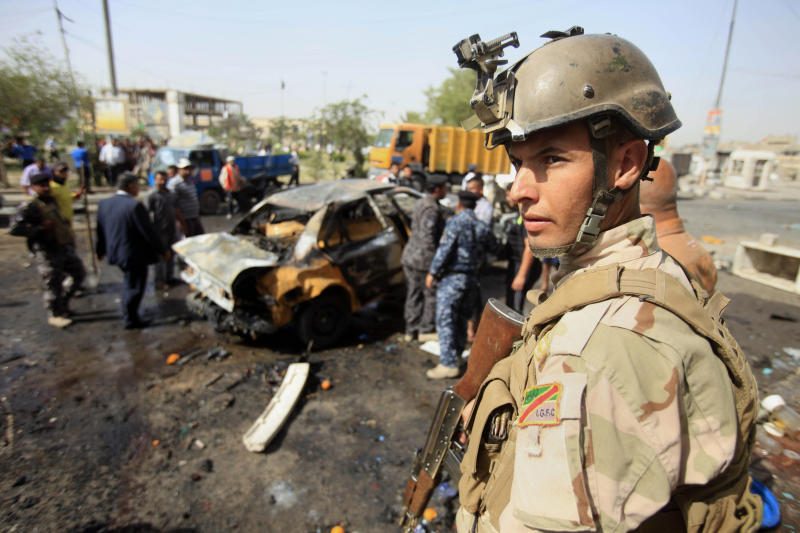 An Iraqi soldier stands guard at the scene of a bomb attack at Sadr City in Baghdad, Iraq, Tuesday, May 28, 2013. A bomb left on a Baghdad minibus and a suicide truck bomb north of the Iraqi capital killed and wounded scores of people on Tuesday, officials said. The attacks followed a particularly bloody day that left more than 70 people dead. (AP Photo/ Karim Kadim)