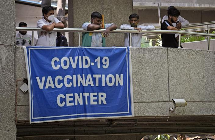 """A sign on a balcony in New Delhi reads """"COVID-19 vaccination center."""""""