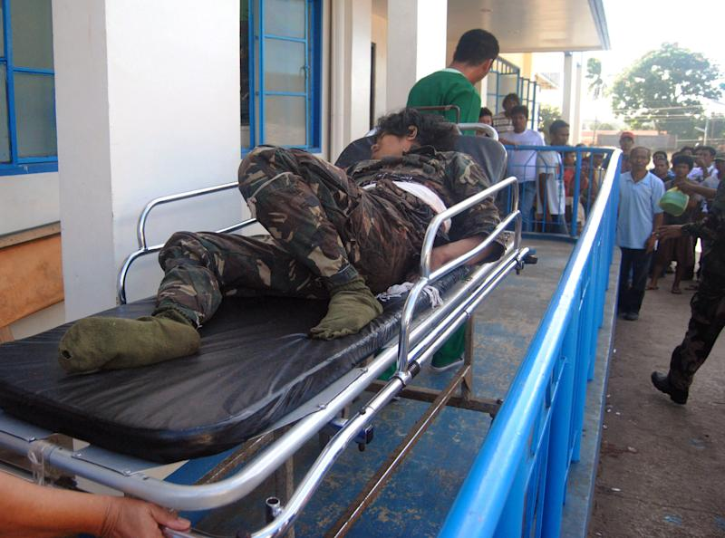 A member of the Moro National Liberation Front, who signed peace with the government more than a decade ago, is rushed for treatment after being wounded in a pursuit of al-Qaida-linked militants who allegedly still in captivity foreign nationals as hostages in the volatile island of Jolo, Sulu province in southern Philippines, Sunday, Feb. 3, 2013. On Saturday,  two Filipino members of a Jordanian TV journalist's crew believed to have been kidnapped by the al-Qaida-linked militants in June, were freed but Jordanian journalist Baker Abdulla Atyani is believed to still be held by the gunmen. (AP Photo/Nickee Butlangan)