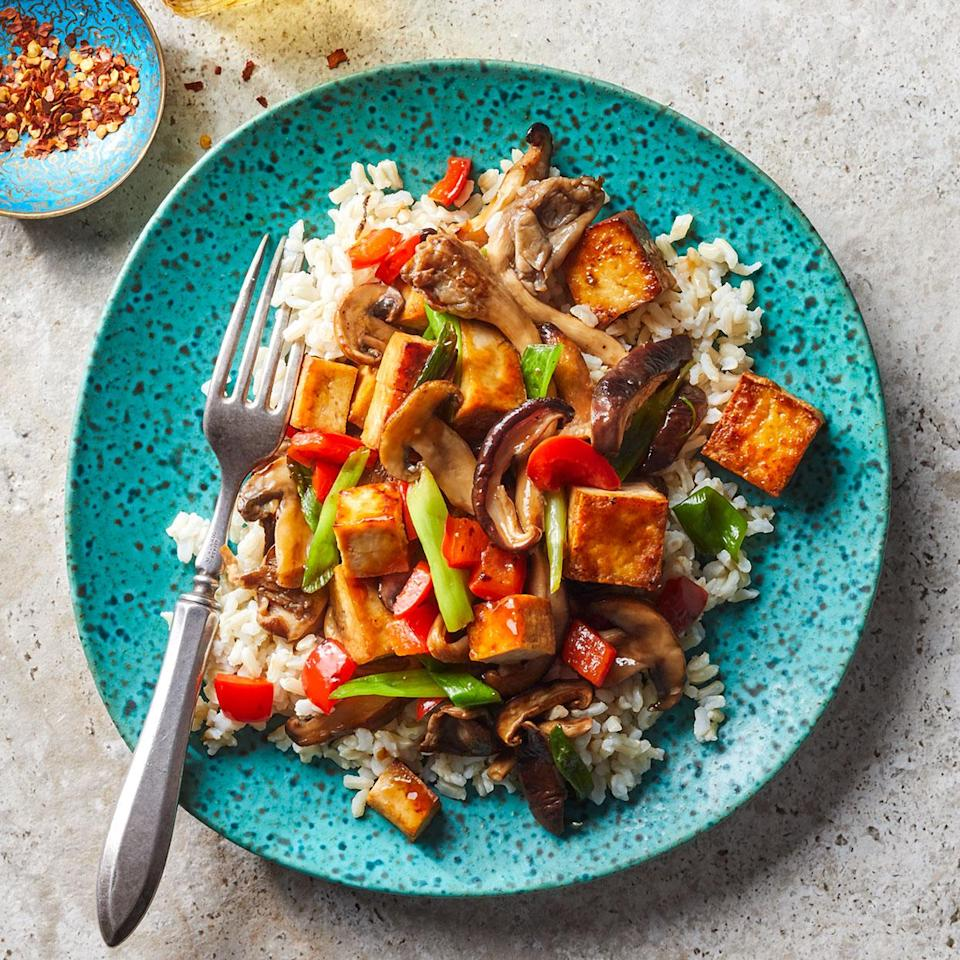 """<p>This tofu veggie stir-fry is quick and easy, making it a great go-to weeknight meal. Baked tofu has a firm, toothsome texture that crisps well in a hot pan. You can find it in flavors like teriyaki and sesame, both of which are delicious here. Or opt for a smoked version, which has the same texture with a more robust flavor. Serve over brown rice.</p> <p> <a href=""""http://www.eatingwell.com/recipe/277158/mushroom-tofu-stir-fry/"""" rel=""""nofollow noopener"""" target=""""_blank"""" data-ylk=""""slk:View recipe"""" class=""""link rapid-noclick-resp""""> View recipe </a></p>"""