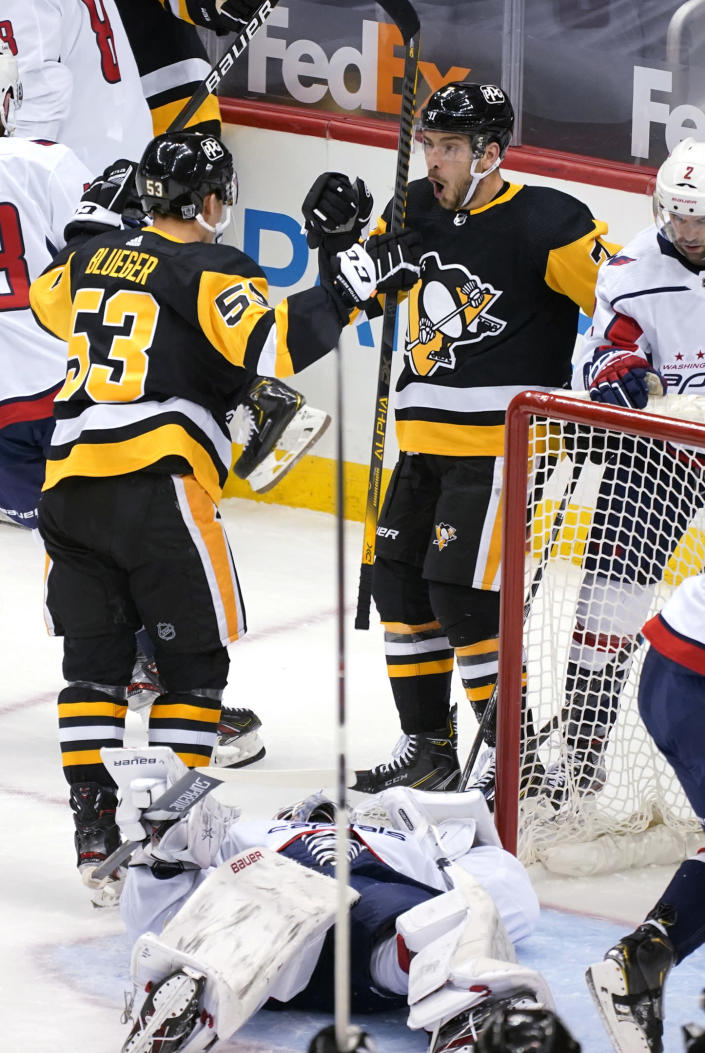 Pittsburgh Penguins' Colton Sceviour (7) celebrates his goal with Teddy Blueger (53) as Washington Capitals goaltender Craig Anderson lies in the goal crease during the first period of an NHL hockey game in Pittsburgh, Tuesday, Jan. 19, 2021. (AP Photo/Gene J. Puskar)