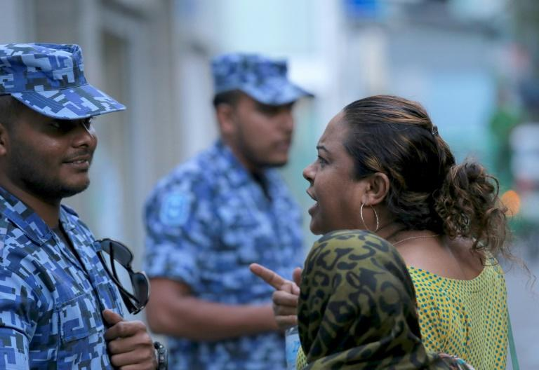 A Maldivian opposition activist argues with a policeman outside parliament on March 27, 2017