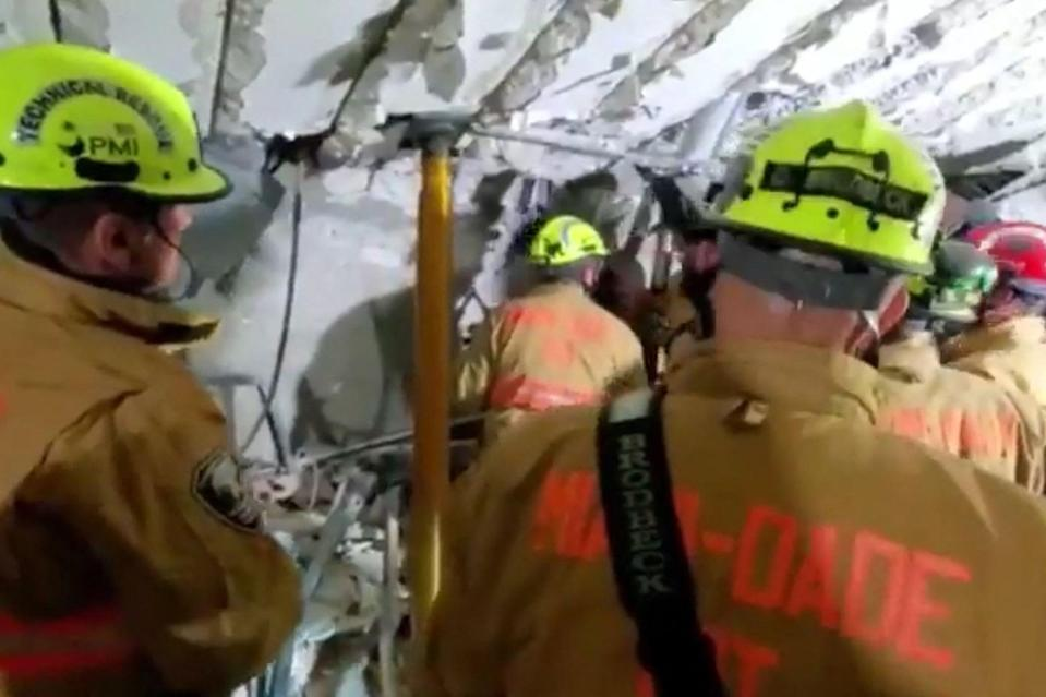 This handout video grab taken from a video posted by the Miami-Dade Fire Rescue shows firefighters working in the basement parking garage (City of Miami Fire-Rescue/AFP vi)