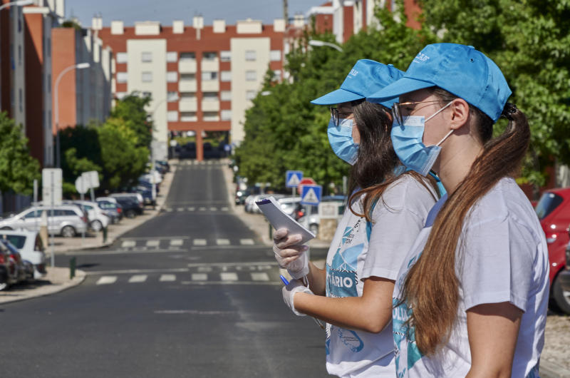 CARCAVELOS, PORTUGAL - JULY 30: Twins Catarina and Dalila Diniz, Cascais Community Program volunteers, wear protective masks and gloves while looking for residents in Bairro dos Diamantes to register them for serologic tests and provide masks to those in need during the COVID-19 Coronavirus pandemic, on July 30, 2020 in Carcavelos, Portugal. Some 300 volunteers participate in a program created by the Municipality of Cascais that offers a test for free for COVID-19 to every resident. Portugal registers to date 1,727 fatalities, 50,868 confirmed cases and 36,140 recovered, and the Government is to approve today changes regarding measures to combat the pandemic. (Photo by Horacio Villalobos#Corbis/Corbis via Getty Images)