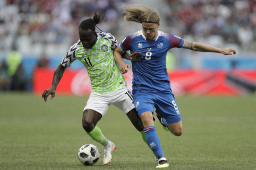 Nigeria's Victor Moses, left, and Iceland's Birkir Bjarnason challenge for the ball during the group D match between Nigeria and Iceland at the 2018 soccer World Cup in the Volgograd Arena in Volgograd, Russia, Friday, June 22, 2018. (AP Photo/Andrew Medichini)