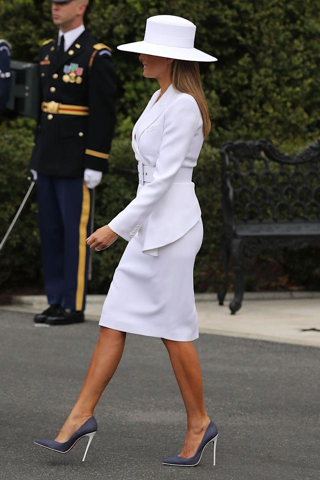 <p>Melania turned heads in this modern white ensemble! She wore an asymmetrical Michael Kors blazer and coordinating pencil skirt, Christian Louboutin pumps, and a wide-brimmed hat to greet French President Emmanuel Macron and his wife, Brigitte. </p>