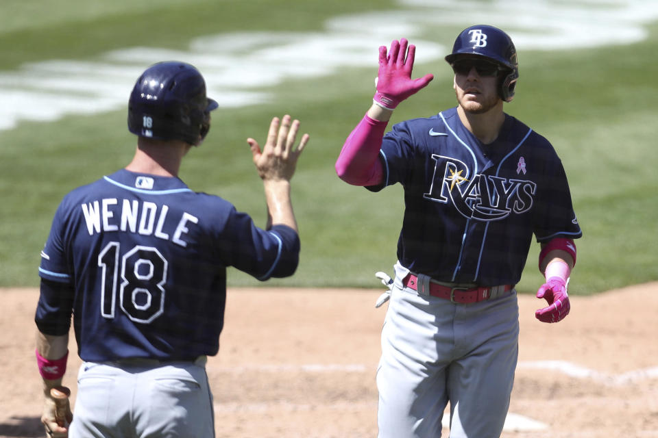 Tampa Bay Rays' Mike Brosseau, right, is congratulated by teammate Joey Wendle after hitting a solo home run against the Oakland Athletics during the sixth inning of a baseball game in Oakland, Calif., Sunday, May 9, 2021. (AP Photo/Jed Jacobsohn)