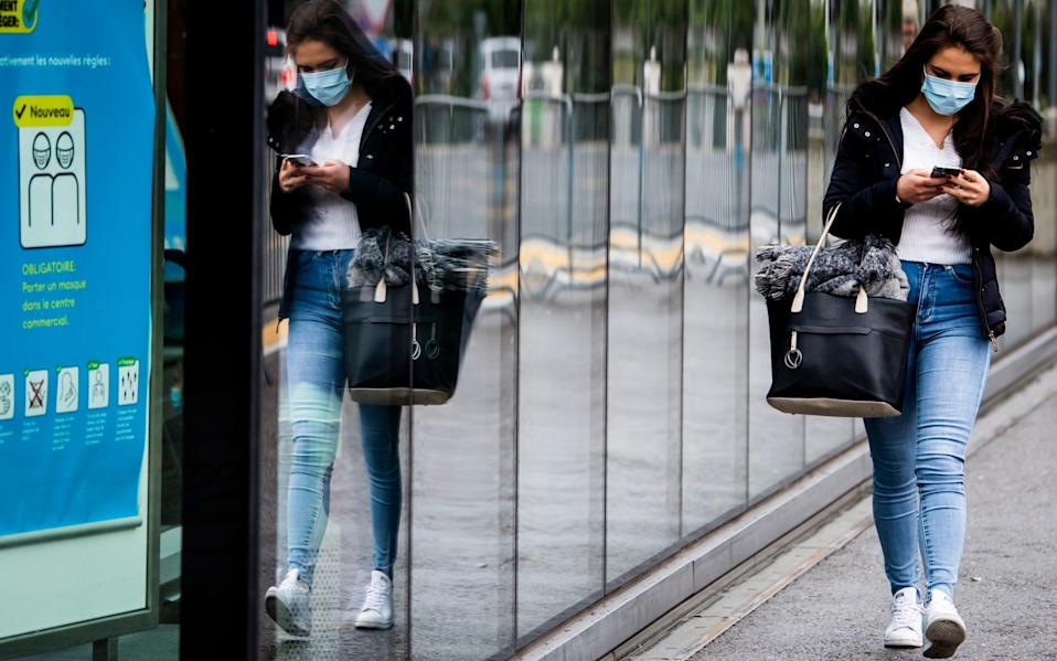 A woman wearing a protective mask in Fribourg, Switzerland, - Jean-Christophe Bott/Keystone via AP