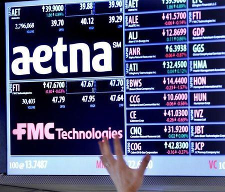 A trader points up at a display on the floor of the New York Stock Exchange August 20, 2012. Health insurer Aetna Inc said on Monday that it would buy rival Coventry Health Care Inc for $5.6 billion to increase its share of the fast-growing, U.S. government-backed Medicare and Medicaid programs. REUTERS/Brendan McDermid (UNITED STATES - Tags: BUSINESS HEALTH LOGO) - RTR36ZMH