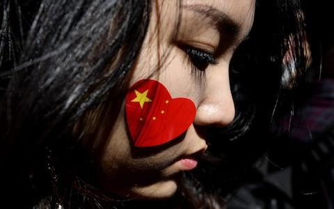 <span>A pro-China activist marches on the streets of Sydney during a rally against ongoing protests in Hong Kong</span> <span>Credit: SAEED KHAN/AFP </span>