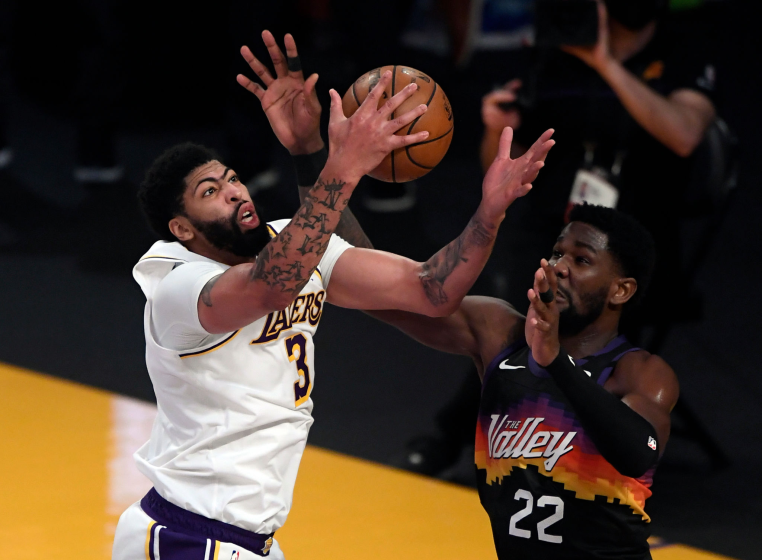 Anthony Davis #3 of the Los Angeles Lakers pulls down a defensive rebound against Deandre Ayton.