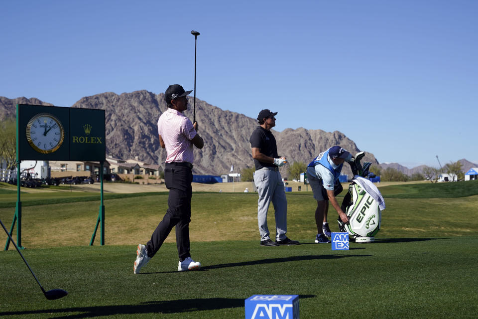 Rickie Folwer, left, hits from the first tee as Phil Mickelson, center, watches during the first round of The American Express golf tournament on the Nicklaus Tournament Course at PGA West, Thursday, Jan. 21, 2021, in La Quinta, Calif. (AP Photo/Marcio Jose Sanchez)