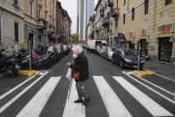 An elderly woman crosses a street in Milan, Italy, Tuesday, Dec. 1, 2020. In Italy, which has the world's second-oldest population, many people in their 70s and older have kept working through the COVID-19 pandemic. From neighborhood newsstand dealers to farmers bring crops to market, they are defying stereotypic labels that depict the old as a monolithic category that's fragile and in need of protection. (AP Photo/Luca Bruno)