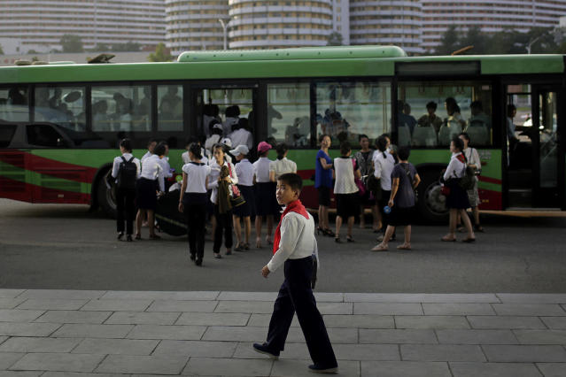 <p>A schoolboy walks toward a carpark as a group of women board a bus in front residential buildings, July 25, 2017, in Pyongyang, North Korea. (Photo: Wong Maye-E/AP) </p>