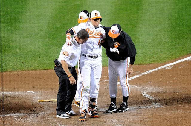 Manny Machado of the Baltimore Orioles is helped off the field after injuring his leg in the third inning against the New York Yankees at Camden Yards on August 11, 2014 in Baltimore (AFP Photo/Greg Fiume)