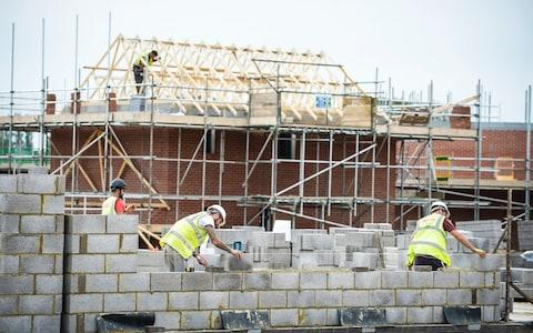 Builders lay blocks on a building site near Bristol - Credit: PA/Ben Birchall